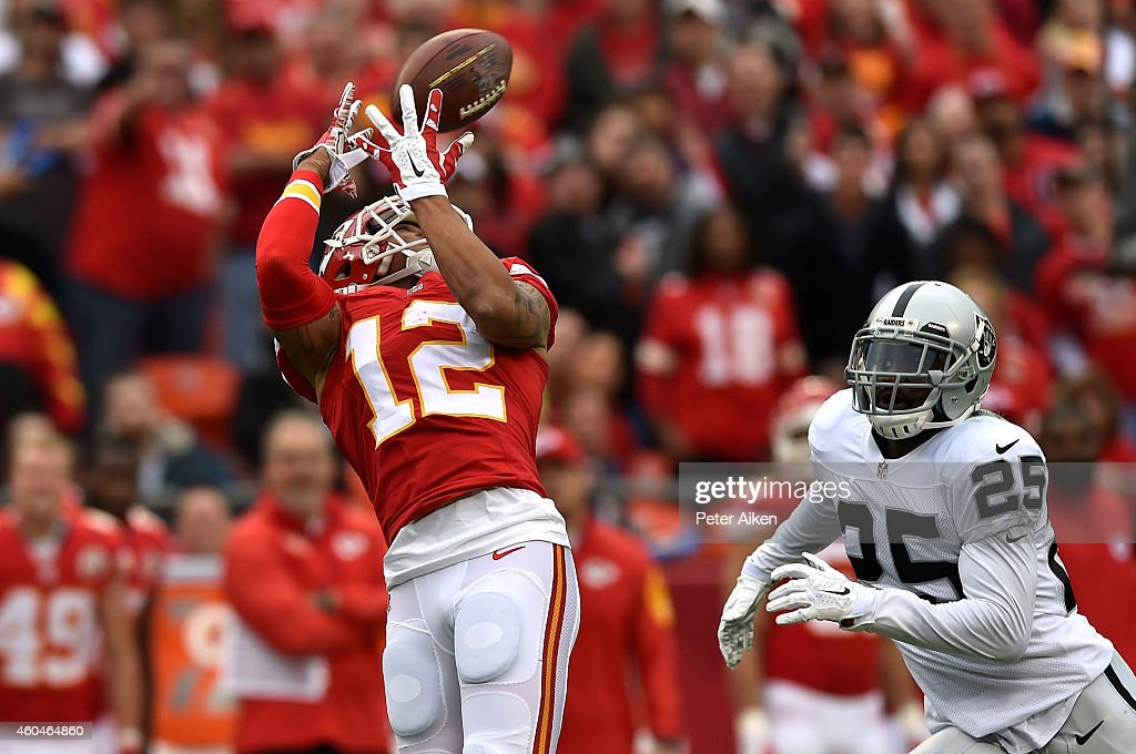Albert Wilson of the Kansas City Chiefs completes a pass as DJ Hayden of the Oakland Raiders defends in the first half at Arrowhead Stadium on...