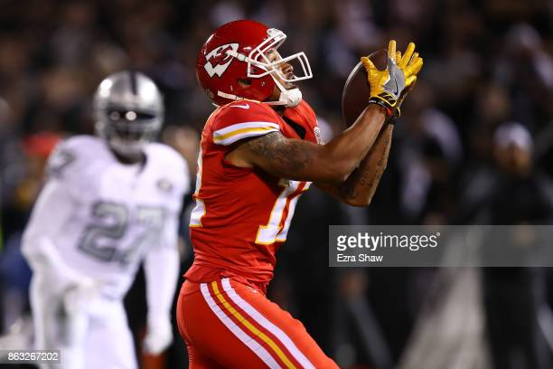Albert Wilson of the Kansas City Chiefs scores on a 63yard touchdown pass that was tipped by Keith McGill II of the Oakland Raiders during their NFL...