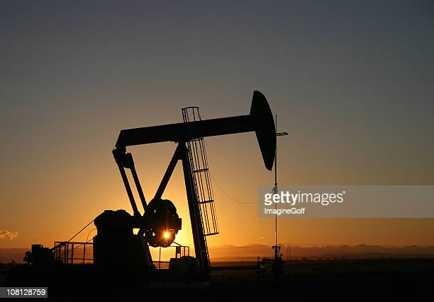 Alberta Pumpjack Silhouette near Calgary With Rocky Mountains
