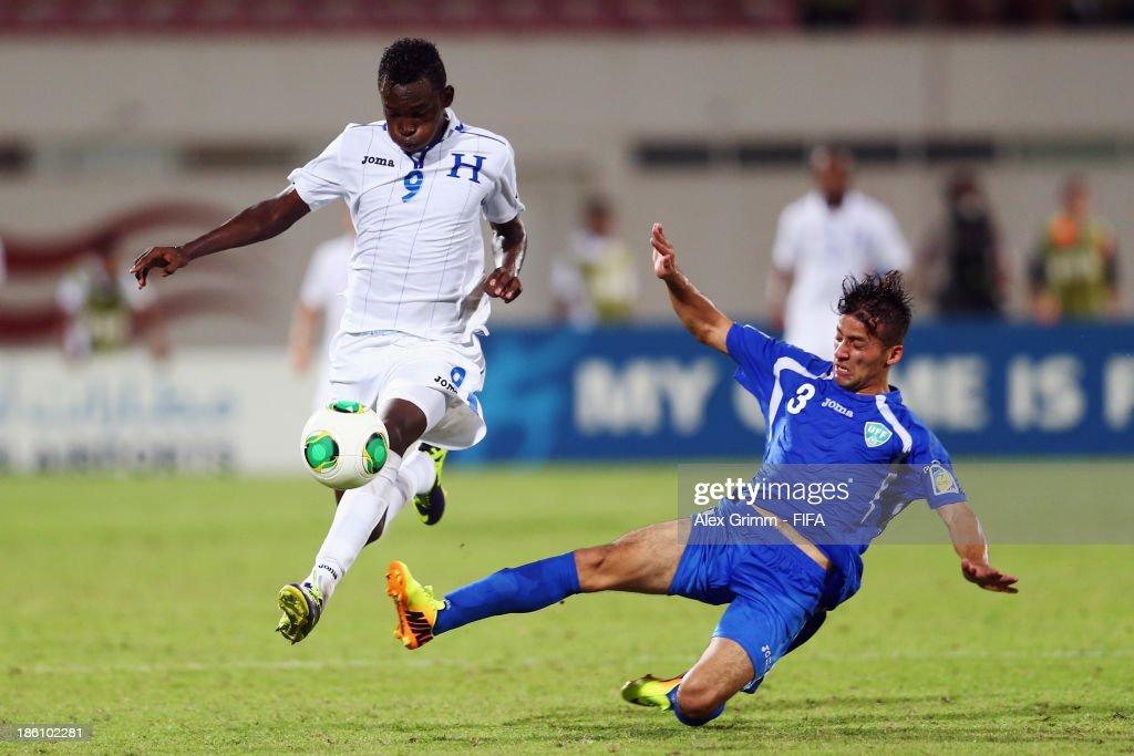 Alberth Elis (L) of Honduras is challenged by Abdulaziz Ashurmatov of Uzbekistan during the FIFA U-17 World Cup UAE 2013 Round of 16 match between Honduras and Uzbekistan at Sharjah Stadium on October 28, 2013 in Sharjah, United Arab Emirates.