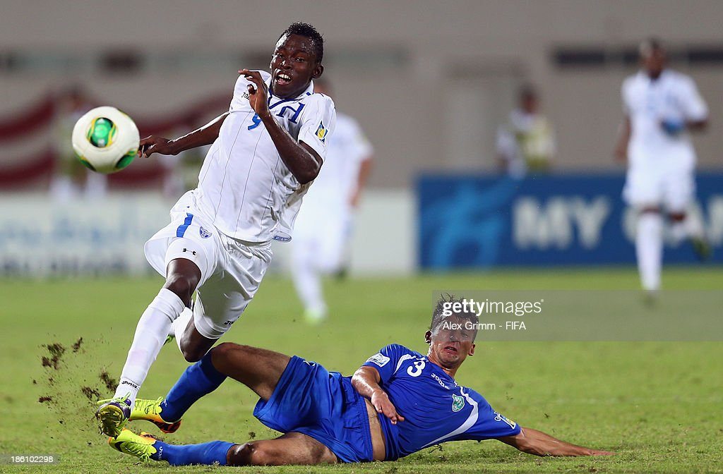 Alberth Elis (L) of Honduras is challenged by Abdulaziz Ashurmatov of Uzbekistan during the FIFA U-17 World Cup UAE 2013 Round of 16 match between Honduras and Uzbekistan at Sharjah Stadium on October 28, 2013 in Sharjah, United Arab Emirates.