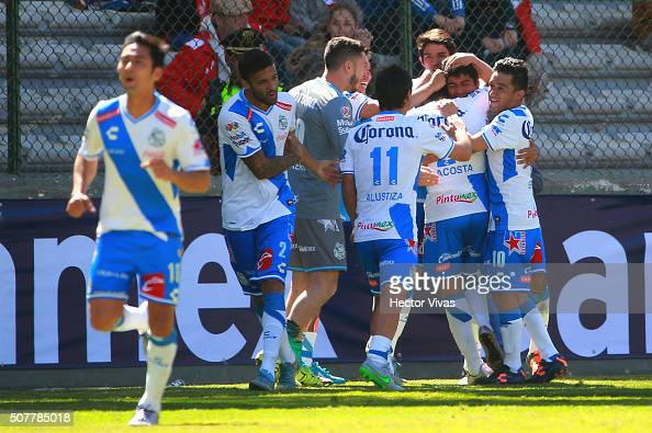 Alberto Acosta of Puebla celebrates with his teammates after scoring the first goal of his team during the fourth round match between Toluca and...
