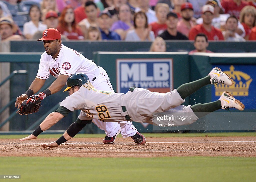 Alberto Callaspo #6 of the Los Angeles Angels dives to tag out Eric Sogard #28 of the Oakland Athletics at third base to end the third inning at Angel Stadium of Anaheim on July 19, 2013 in Anaheim, California.
