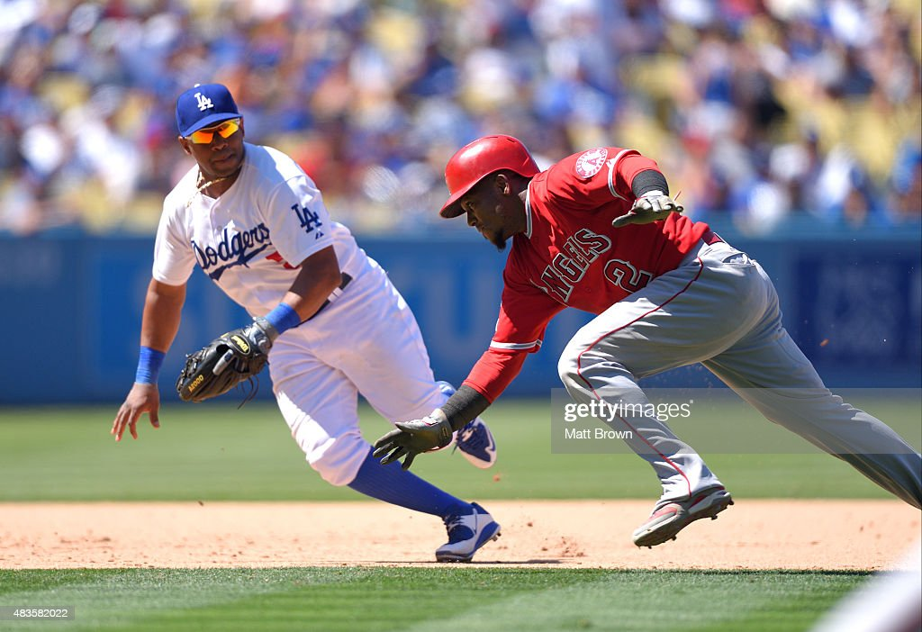 Alberto Callaspo #5 of the Los Angeles Dodgers tags out Erick Aybar #2 of the Los Angeles Angels of Anaheim as he attempts to reach third base during the seventh inning of the game at Dodger Stadium on August 2, 2015 in Los Angeles, California.