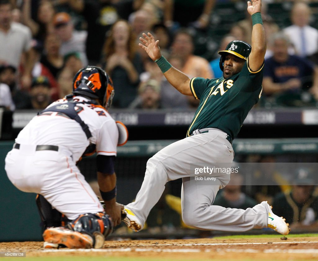 Alberto Callaspo #7 of the Oakland Athletics is tagged out by Carlos Corporan #22 of the Houston Astros trying to score in the fifth inning at Minute Maid Park on August 27, 2014 in Houston, Texas.