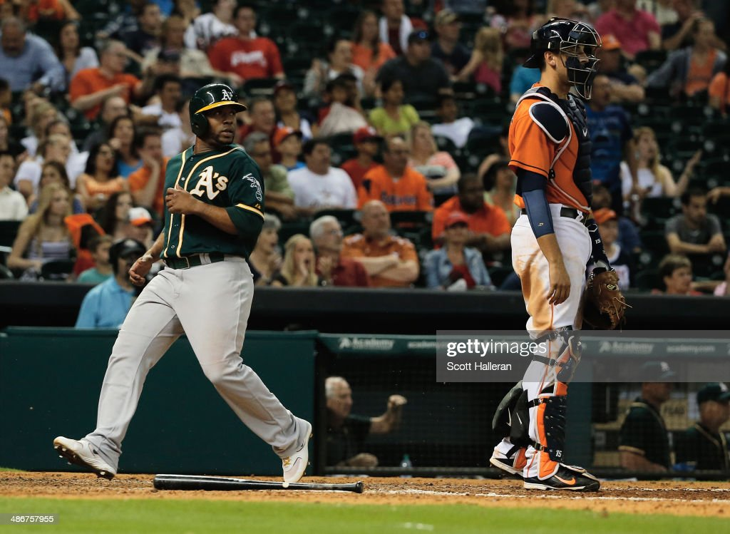 Alberto Callaspo #18 of the Oakland Athletics scores the go-ahead run in the ninth inning as Jason Castro #15 of the Houston Astros looks on during their game at Minute Maid Park on April 25, 2014 in Houston, Texas.