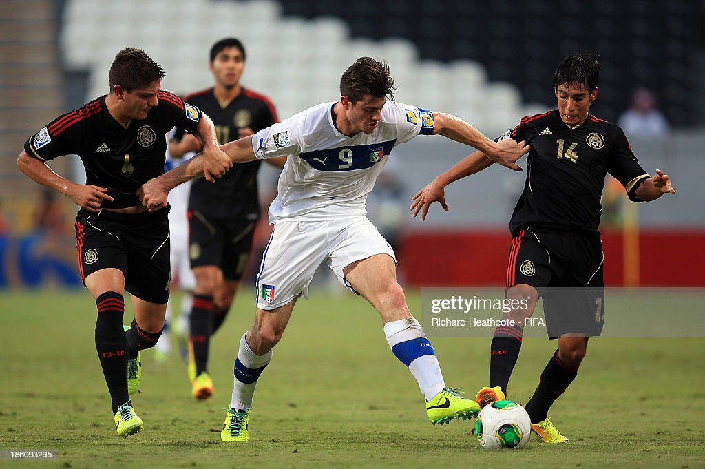 Alberto Cerri of Italy holds off Pedro Teran and Erick Aguirre of Mexico during the FIFA U-17 World Cup UAE 2013 Round of 16 match between Italy and Mexico at the Mohamed Bin Zayed Stadium on October 28, 2013 in Abu Dhabi, United Arab Emirates.