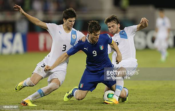 Alberto Cerri of Italy is tackled by Facundo Ospitaleche and Fabrizio Buschiazzo of Uruguay during the Group B FIFA U17 World Cup match between Italy...