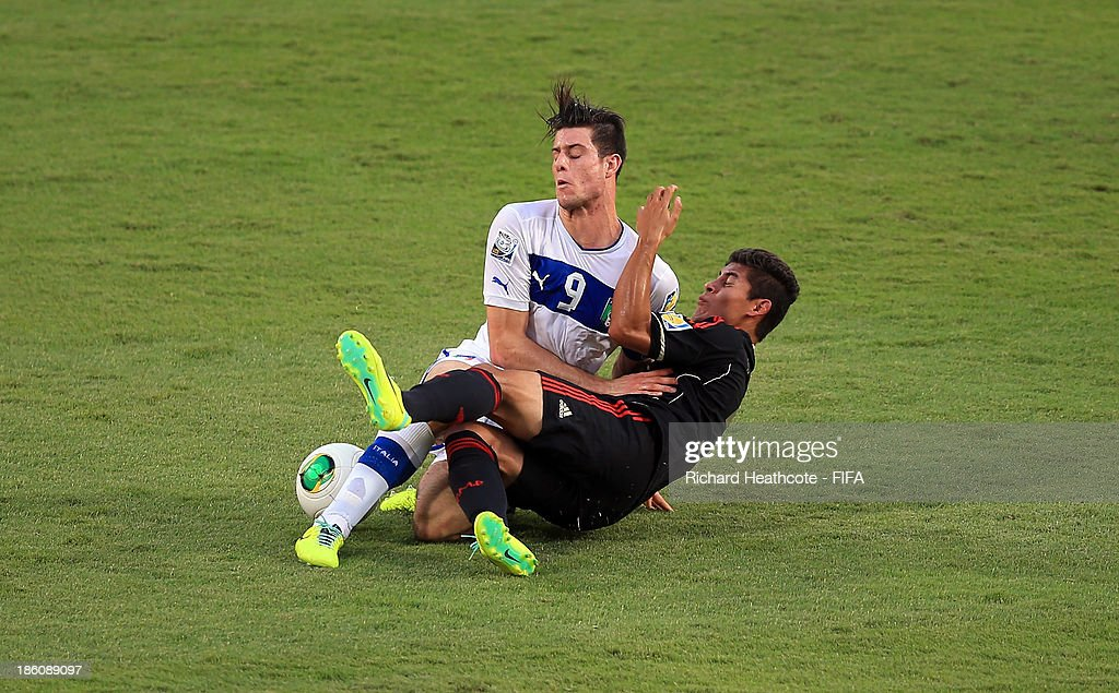 Alberto Cerri of Italy is tackled by Salomon Wbias of Mexico during the FIFA U-17 World Cup UAE 2013 Round of 16 match between Italy and Mexico at the Mohamed Bin Zayed Stadium on October 28, 2013 in Abu Dhabi, United Arab Emirates.
