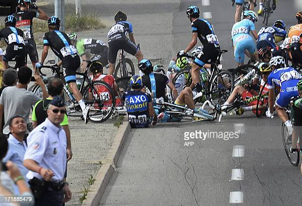 Alberto Contador of Spain center with number 91 sits on the road after a group of riders crashed during the first stage of the Tour de France cycling...