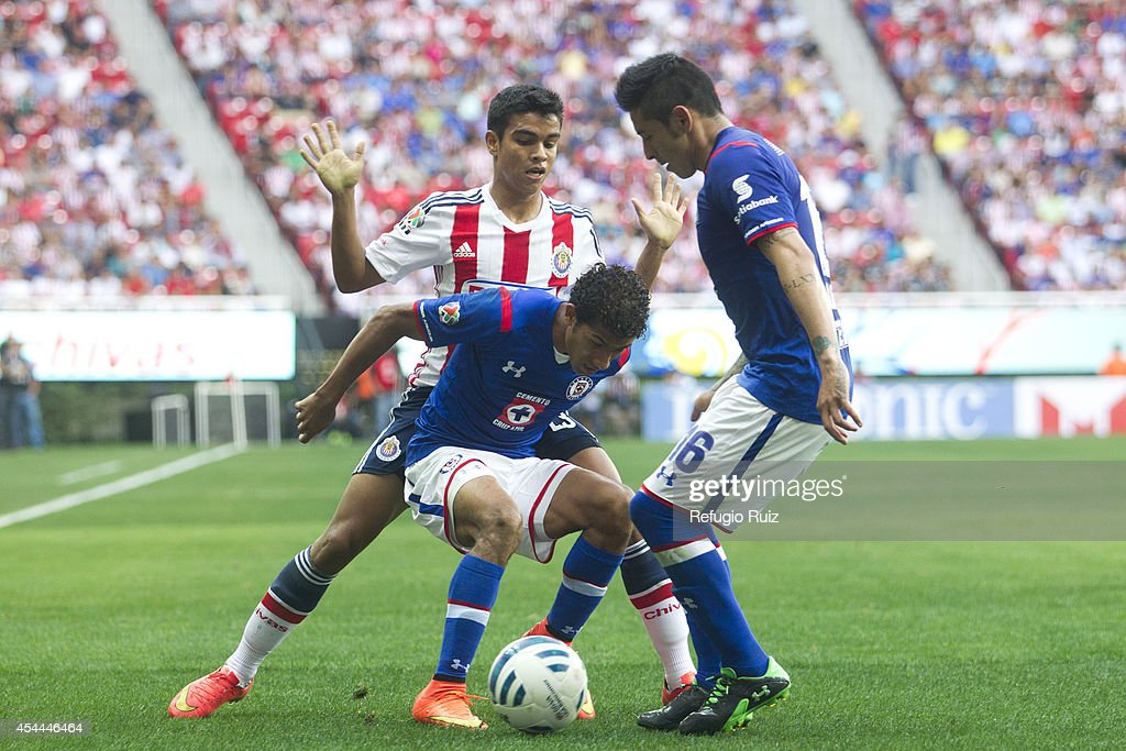 Alberto Garcia of Chivas fights for the ball with Joao Rojas of Cruz Azul during a match between Chivas and Cruz Azul a as part of Apertura 2014 Liga MX at Omnilife Stadium on August 31, 2014 in Guadalajara, Mexico.