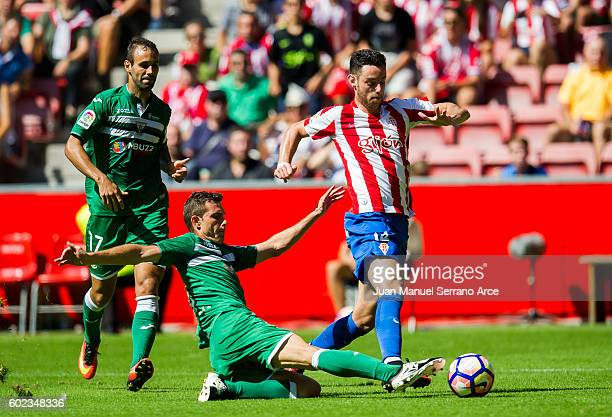Alberto Martin of Club Deportivo Leganes duels for the ball with Jorge Franco 'Burgui' of Real Sporting de Gijon during the La Liga match between...