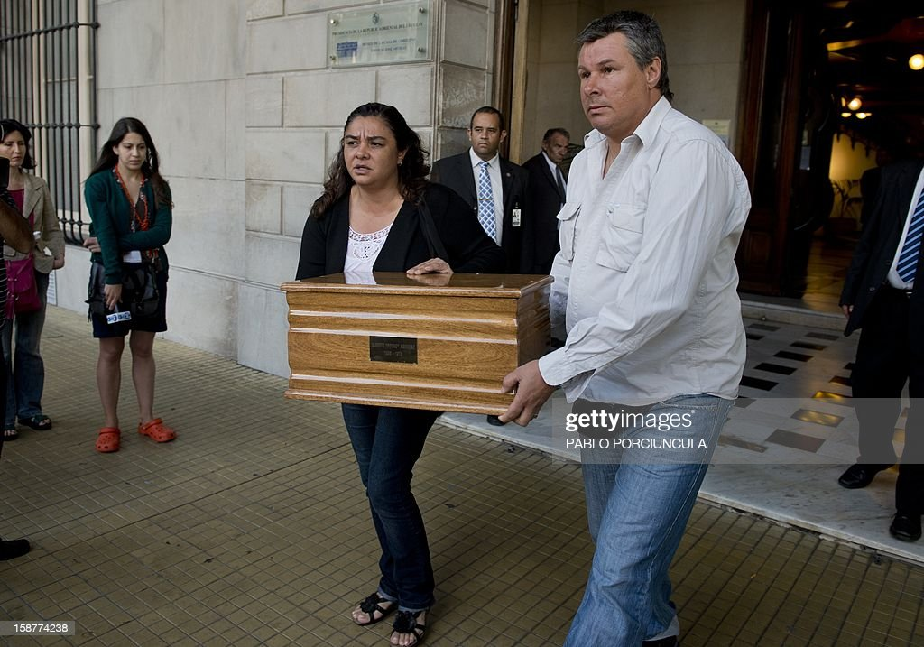 Alberto Mechoso (R) and his sister Beatriz carry the urn with remains of their father the Uruguayan anarchist Alberto Mechoso, disappeared in Buenos Aires in 1976 during Argentine military dictatorship, after a ceremony in Montevideo on December 28, 2012. The Uruguayan Government gave the remains of Mechoso to his relatives after being identified in Argentina. Mechoso was detained in September 26, 1976 and he was seen for the last time at the clandestine detention centre Automotoras Orletti on that year. AFP PHOTO/Pablo PORCIUNCULA