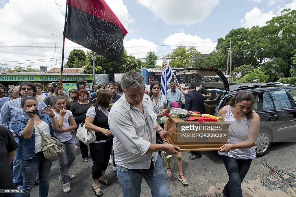 Alberto Mechoso (L) and his sister Beatriz carry the urn with the remains of their father, Uruguayan anarchist Alberto Mechoso --disappeared in Buenos Aires in 1976 during Argentina's military dictatorship-- during his funeral in Montevideo on December 28, 2012. The Uruguayan Government gave the remains of Mechoso to his relatives after being identified in Argentina. Mechoso was detained in September 26, 1976 and he was seen for the last time at the clandestine detention centre Automotoras Orletti on that year. AFP PHOTO/Pablo PORCIUNCULA