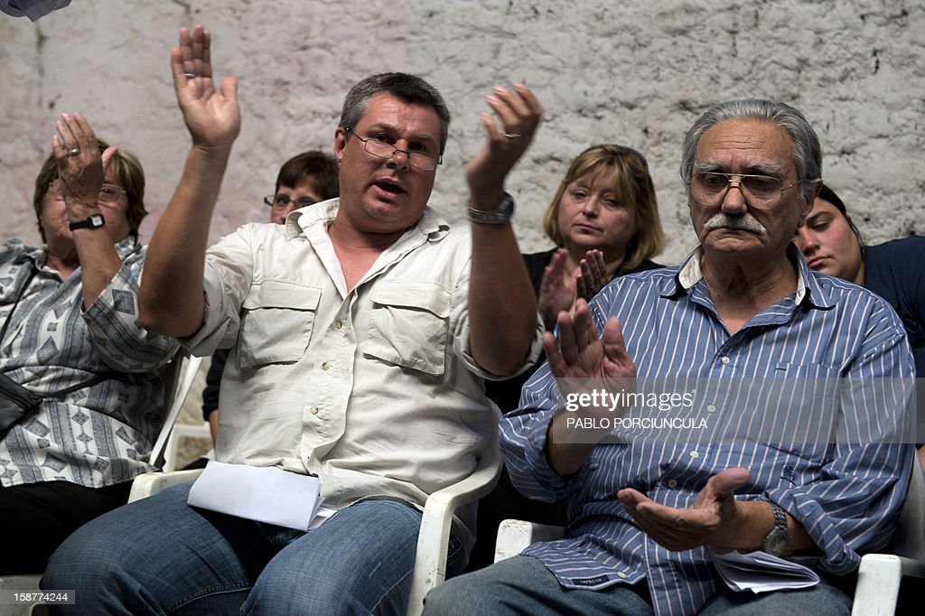 Alberto Mechoso (L) and Juan Carlos, son and brother (respectively) of the Uruguayan anarchist Alberto Mechoso, clap during his wake on December 28, 2012 in Montevideo. The Uruguayan Government gave the remains of Mechoso to his relatives after being identified in Argentina. Mechoso was detained in September 26, 1976 and he was seen for the last time at the clandestine detention centre Automotoras Orletti on that year. AFP PHOTO/Pablo PORCIUNCULA
