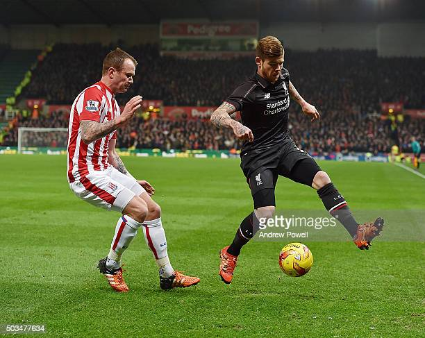 Alberto Moreno of Liverpool competes with Glenn Whelan of Stoke City during the Capital One Cup semi final first leg match between Stoke City and...