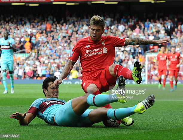 Alberto Moreno of Liverpool competes with James Tomkins of West Ham United during the Barclays Premier League match between Liverpool and West Ham...