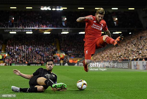 Alberto Moreno of Liverpool hurdles the challenge from Guillermo Cotugno of Rubin Kazan during the UEFA Europa League Group B match between Liverpool...