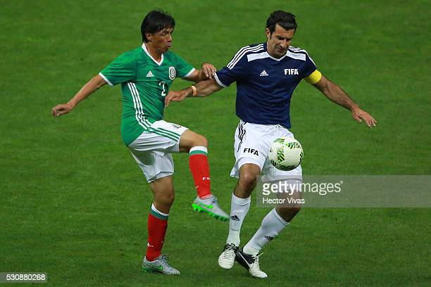 Alberto Rodriguez of Mexico's All Star Team struggles for the ball with Luis Figo of FIFA Football Legends during the FIFA Football Legends Match...