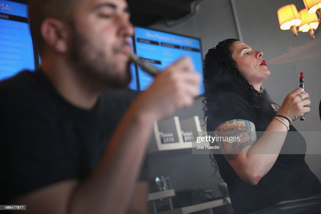 Alberto Roque (L) and Julia Boyle wait for customers as they enjoy an electronic cigarette at the Vapor Shark store on April 24, 2014 in Miami, Florida. Brandon Leidel, CEO, Director of Operations Vapor Shark, said he welcomes the annoucement by the Food and Drug Administration that they are proposing the first federal regulations on electronic cigarettes, which would ban sales of the popular devices to anyone under 18 and require makers to gain FDA approval for their products.