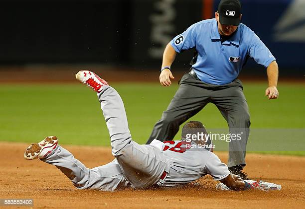 Alberto Rosario of the St Louis Cardinals slides into second base with a double as umpire Mike Muchlinski looks on against the New York Mets in the...