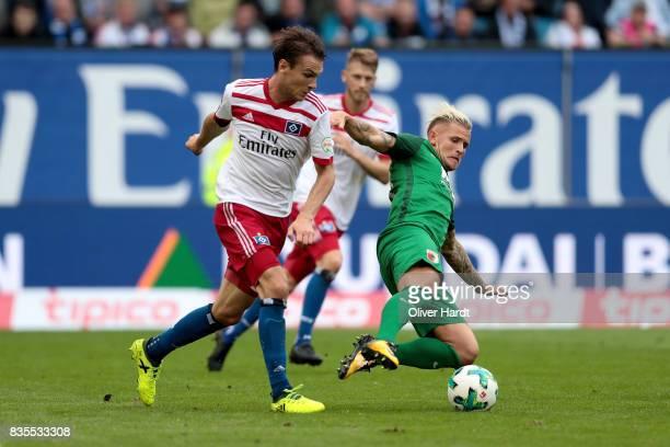 Albin Ekdal of Hamburg and Philipp Max of Augsburg compete for the ball during the Bundesliga match between Hamburger SV and FC Augsburg at...