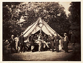 Albumen print of a Union Army hospital tent on the battlefield at Gettysburg An injured man lies on a table while the surgeon stands nearby with a...