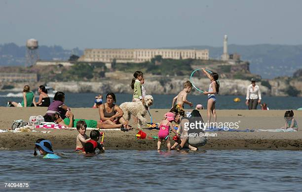 Alcatraz Island sits in the background as people play on the beach at Crissy Field May 7 2007 in San Francisco California The Bay Area is...