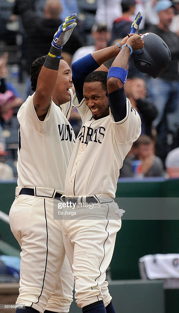 Alcides Escobar #2 celebrates with Salvador Perez #13 of the Kansas City Royals after scoring on Kendrys Morales' two-run walk-off home run in the 13th inning against the Atlanta Braves at Kauffman Stadium on May 15, 2016 in Kansas City, Missouri. The Royals won 4-2.