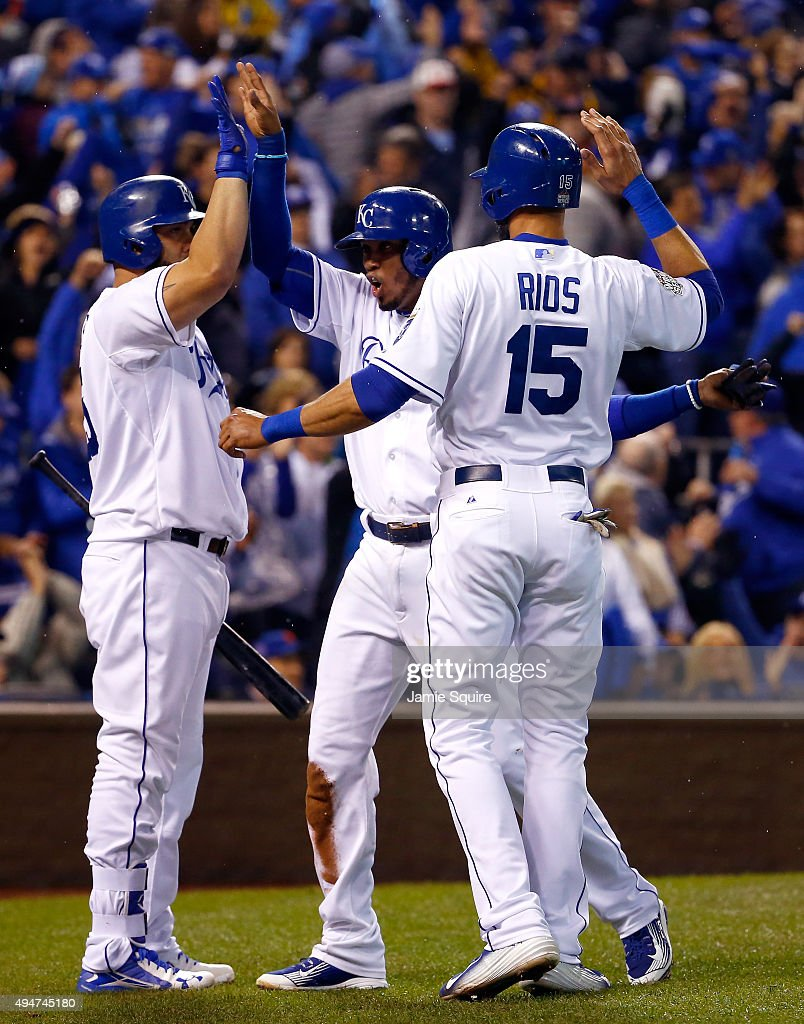 Alcides Escobar #2 of the Kansas City Royals and Alex Rios #15 of the Kansas City Royals celebrate with Kendrys Morales #25 of the Kansas City Royals after scoring runs in the fifth inning against the New York Mets in Game Two of the 2015 World Series at Kauffman Stadium on October 28, 2015 in Kansas City, Missouri.