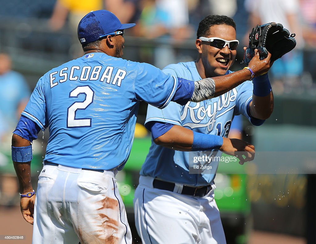 Alcides Escobar #2 of the Kansas City Royals and Salvador Perez #13 celebrate a 4-1 win against the Cleveland Indians at Kauffman Stadium on June 11, 2014 in Kansas City, Missouri.