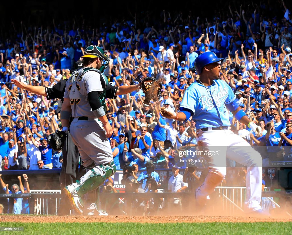Alcides Escobar of the Kansas City Royals celebrates after sliding into home plate to score during the 7th inning of the game against the Oakland...