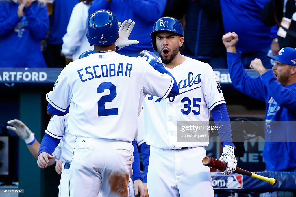 Alcides Escobar of the Kansas City Royals celebrates with teammate Eric Hosmer after scoring the lead off run of Ben Zobrist single in the seventh...