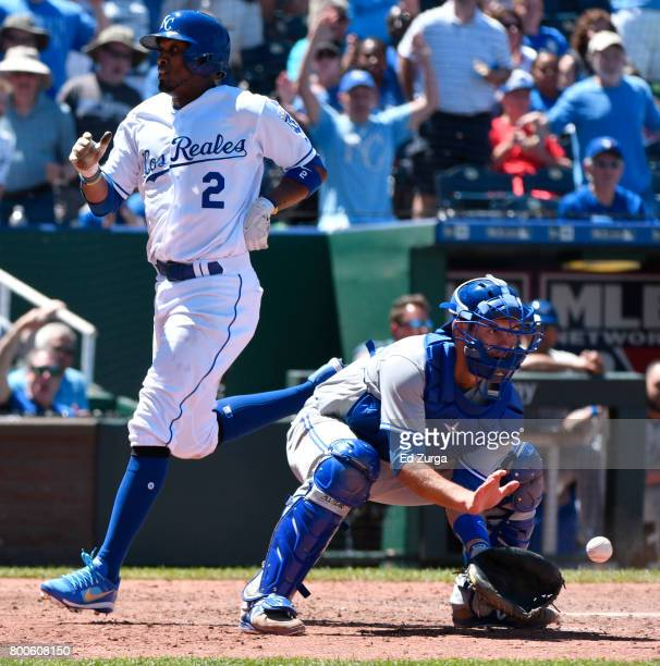 Alcides Escobar of the Kansas City Royals crosses home to score past Luke Maile of the Toronto Blue Jays in the seventh inning at Kauffman Stadium on...