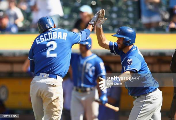 Alcides Escobar of the Kansas City Royals is congratulated by Drew Butera after he scored in the ninth inning against the Oakland Athletics at...