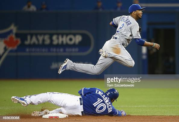 Alcides Escobar of the Kansas City Royals jumps over Edwin Encarnacion of the Toronto Blue Jays to turn a double play to end the fourth inning during...