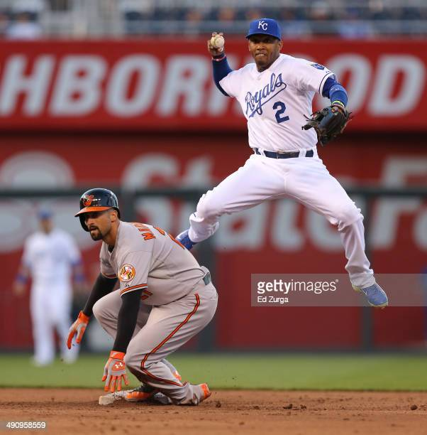 Alcides Escobar of the Kansas City Royals leaps away from Nick Markakis of the Baltimore Orioles as he throws to first on a double play attempt in...