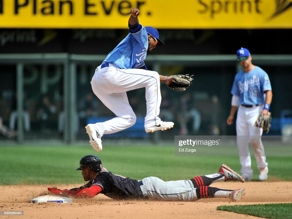 Alcides Escobar #2 of the Kansas City Royals leaps over Francisco Lindor #12 of the Cleveland Indians as Lindor slides safely into second for a steal in the fifth inning at Kauffman Stadium on August 20, 2017 in Kansas City, Missouri.