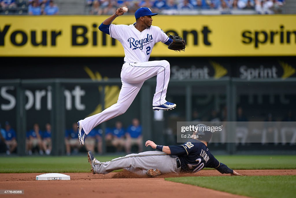 <a gi-track='captionPersonalityLinkClicked' href=/galleries/search?phrase=Alcides+Escobar&family=editorial&specificpeople=4845889 ng-click='$event.stopPropagation()'>Alcides Escobar</a> #2 of the Kansas City Royals leaps over <a gi-track='captionPersonalityLinkClicked' href=/galleries/search?phrase=Jonathan+Lucroy&family=editorial&specificpeople=5732413 ng-click='$event.stopPropagation()'>Jonathan Lucroy</a> #20 of the Milwaukee Brewers as he throws to first on a double play attempt at Kauffman Stadium on June 18, 2015 in Kansas City, Missouri. Lucroy was out and Ryan Braun was safe at first.