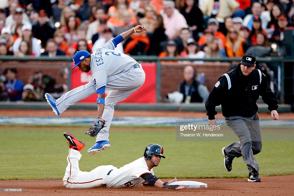 <a gi-track='captionPersonalityLinkClicked' href=/galleries/search?phrase=Alcides+Escobar&family=editorial&specificpeople=4845889 ng-click='$event.stopPropagation()'>Alcides Escobar</a> #2 of the Kansas City Royals leaps to catch a ball as <a gi-track='captionPersonalityLinkClicked' href=/galleries/search?phrase=Gregor+Blanco&family=editorial&specificpeople=4137600 ng-click='$event.stopPropagation()'>Gregor Blanco</a> #7 of the San Francisco Giants advances on a wild pitch in the first inning during Game Four of the 2014 World Series at AT&T Park on October 25, 2014 in San Francisco, California.