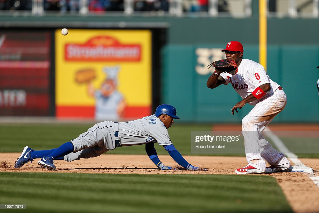 <a gi-track='captionPersonalityLinkClicked' href=/galleries/search?phrase=Alcides+Escobar&family=editorial&specificpeople=4845889 ng-click='$event.stopPropagation()'>Alcides Escobar</a> #2 of the Kansas City Royals safely dives back to first base before the tag by <a gi-track='captionPersonalityLinkClicked' href=/galleries/search?phrase=Ryan+Howard&family=editorial&specificpeople=551402 ng-click='$event.stopPropagation()'>Ryan Howard</a> #6 of the Philadelphia Phillies in the third inning during the home opener at Citizens Bank Park on April 5, 2013 in Philadelphia, Pennsylvania.