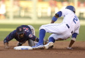 Alcides Escobar of the Kansas City Royals slides into second for a double as Alexi Casilla of the Minnesota Twins is late with the tag in the first...