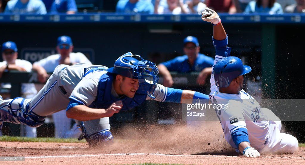 Alcides Escobar #2 of the Kansas City Royals slides safely into home to score past the tag of Luke Maile #22 of the Toronto Blue Jays in the third inning at Kauffman Stadium on June 24, 2017 in Kansas City, Missouri. Escobar scored from third on Whit Merrifield's #15 sacrifice fly.
