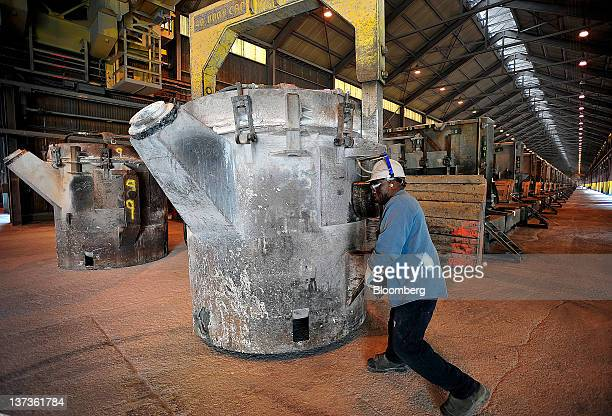 Alcoa Inc employee Clarence Benjamin pushes a crucible of molten aluminum into place for transport at the company's Mt Holly production plant in...