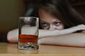 Alcohol addict looking at glass of whiskey with desire