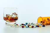 Whiskey glass, with ice cubes, beside a large amount of drugs, capsules and pills spread around and falling out of the recipient on a white background.