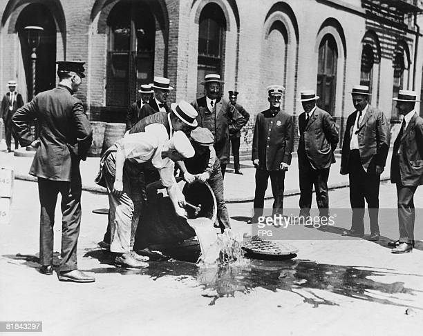 Alcohol is poured away into a New York sewer during the prohibition era circa 1920