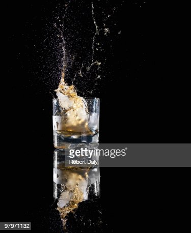 Alcohol spilling from highball glass : Stock Photo
