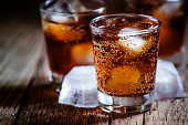 Alcoholic cocktail with cola and whiskey and ice cubes, vintage wooden background, selective focus