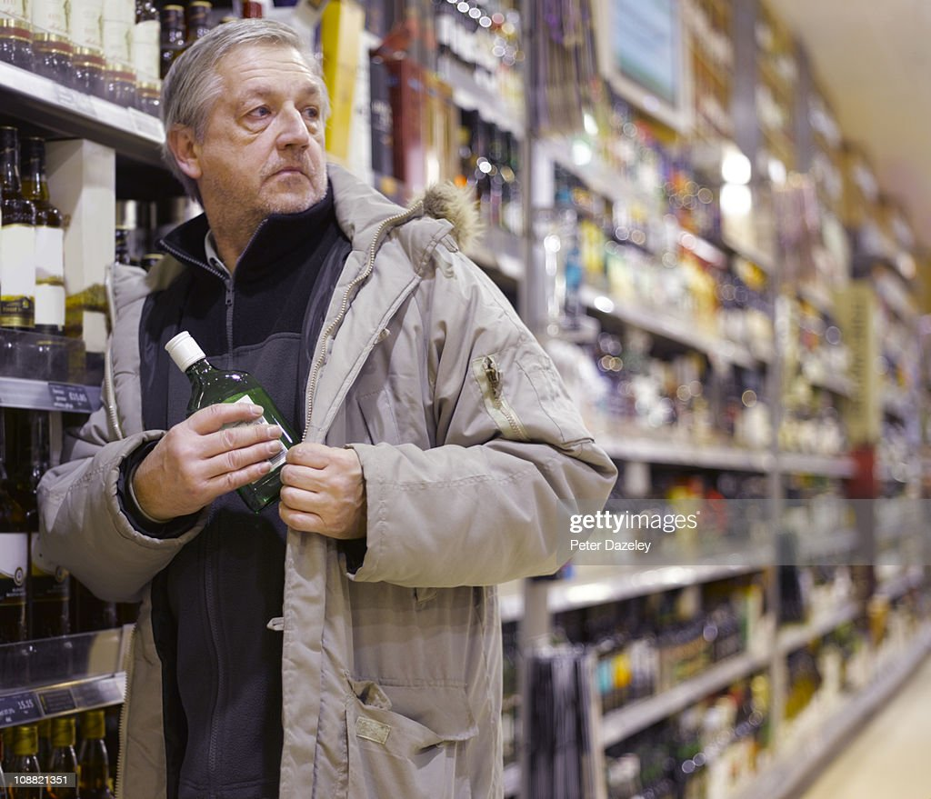 Alcoholic stealing gin from supermarket : Stock Photo